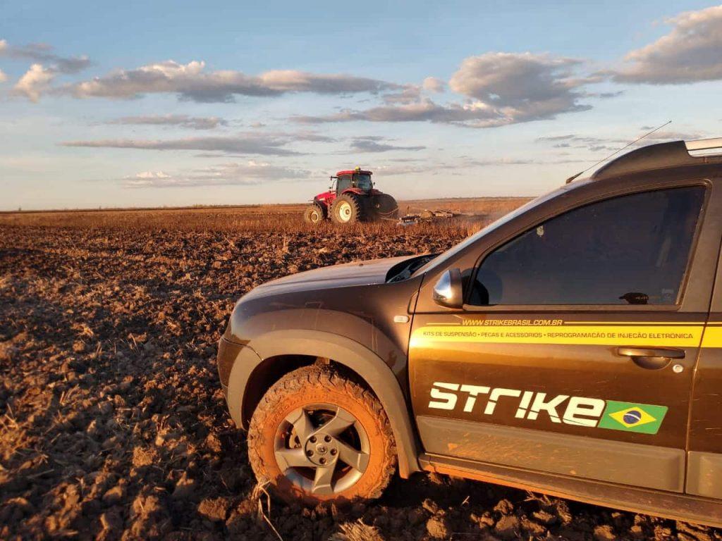 Remap em máquinas agrícolas - saveiro preta do atendimento da Strike Brasil no campo, na frente de um trator vermelho